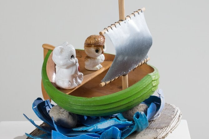 Wooden boat sculpture with plastic cat and owl inside