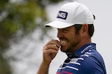 Louis Oosthuizen grimaces while holding his hand up to his mouth after putting during the US Open golf.