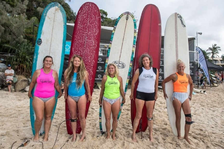 Five women stand in a line in front of their surfboards on a beach.