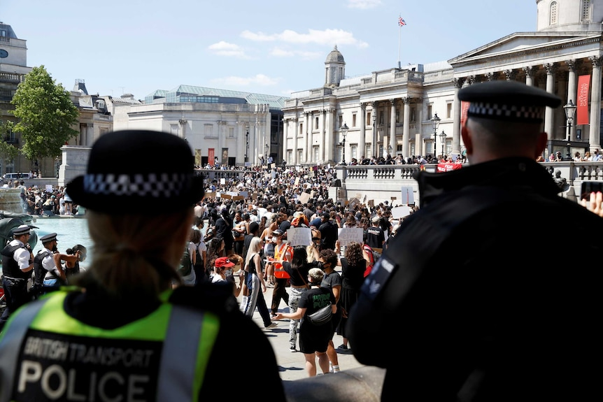 You look on at a protest filling London's Trafalgar Square from behind two British police officers on a clear day.