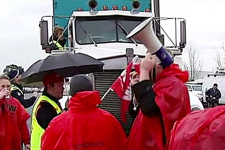 Coles employees stop a truck at the picket line.