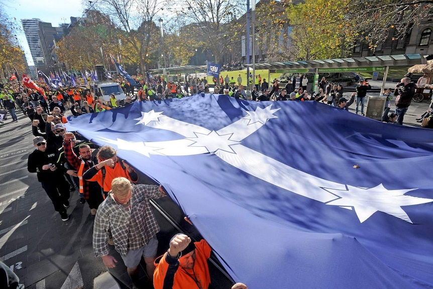 Building and construction workers march down Swanston Street with a Southern Cross flag unfurled.
