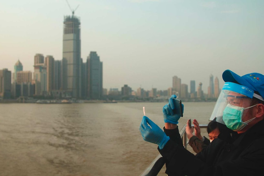 A masked tourist takes a photo of his ticket aboard a ferry on the Yangtze River in front of Wuhan's skyline.