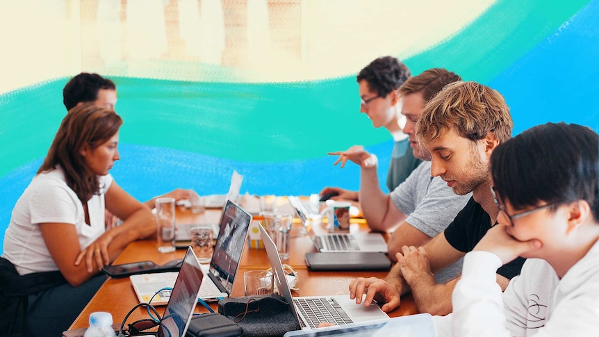 Group of men and women working on their laptops at a large desk for a story about the dark side of entrepreneurship