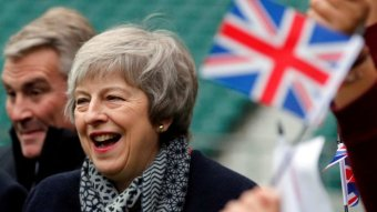 Theresa May is seen laughing while a person waves a small British flag that is out of focus