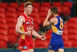 A young AFL player pumps his fists in celebration at the end of a game.