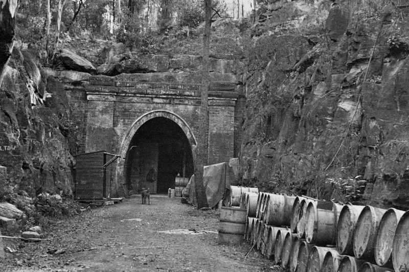 The entrance to a large underground tunnel, surrounded by rock walls, with storage drums in the foreground.