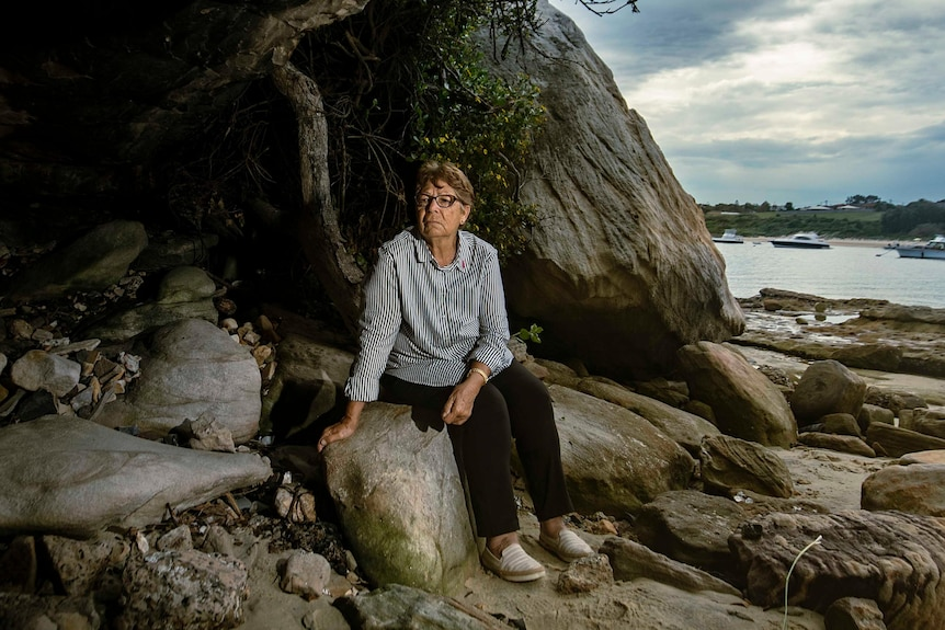 Aboriginal elder Aunty Barbara Simms sits on the rock at the edge of a dark cave with a quiet bay behind her.