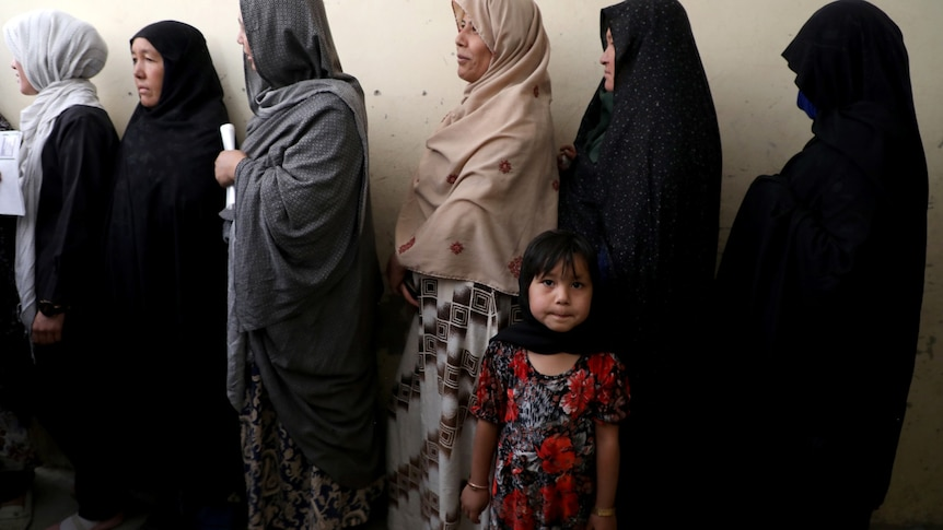A girl looks at the camera next to a  line of women in head scarves