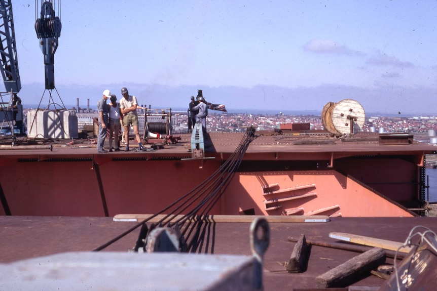 Workers stand on a large metal platform, port in background.