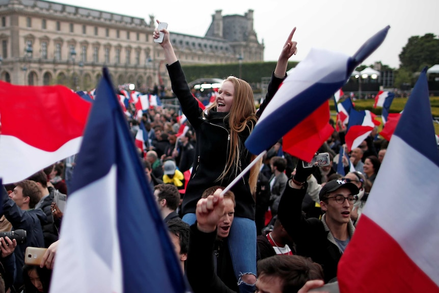 Supporters of Emmanuel Macron celebrate and wave flags near the Louvre museum after the French election results were announced.