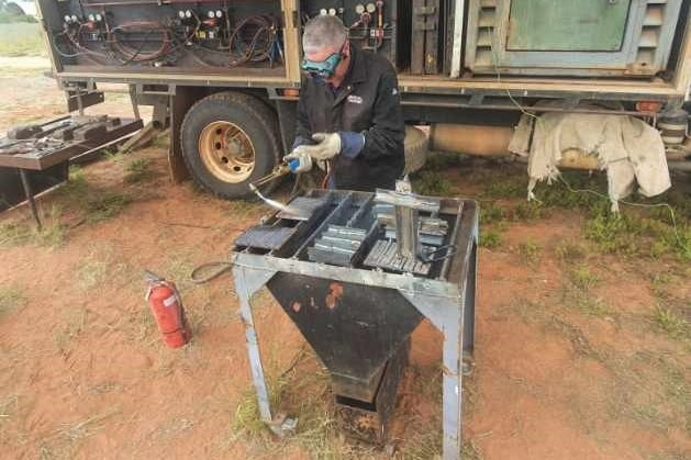 A man with grey hair works at a welding table.
