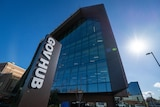 A close-up shot of a big glass building with the sign 'GovHub' out the front. Blue sunny sky in background.