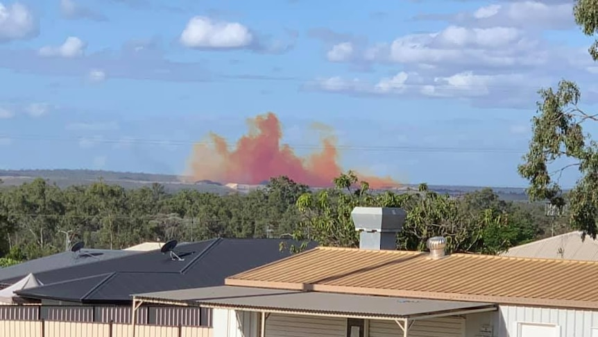 An orange and red plume of chemical, dust and smoke can be seen from houses.