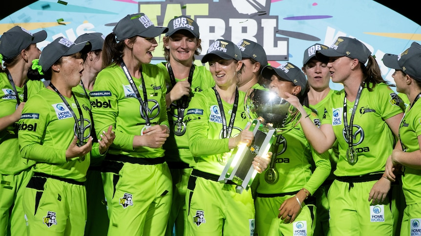 Sydney Thunder players smiles and stand around a large silver trophy in front of a colourful backdrop