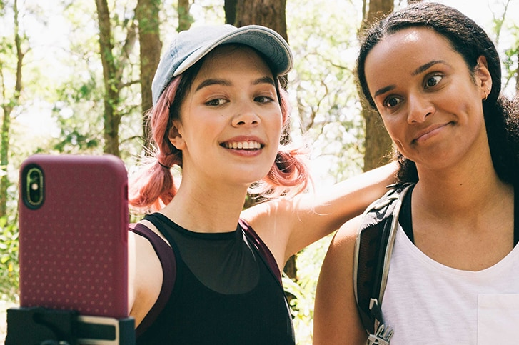 Two girls wearing active wear pose for a selfie during a hike on a sunny day in front of trees.
