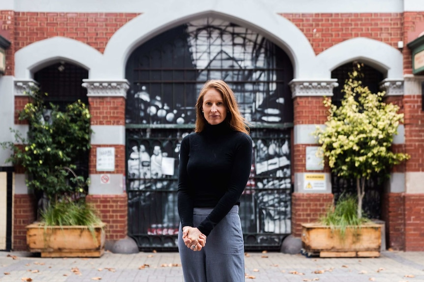 Woman stands outside closed gate of building