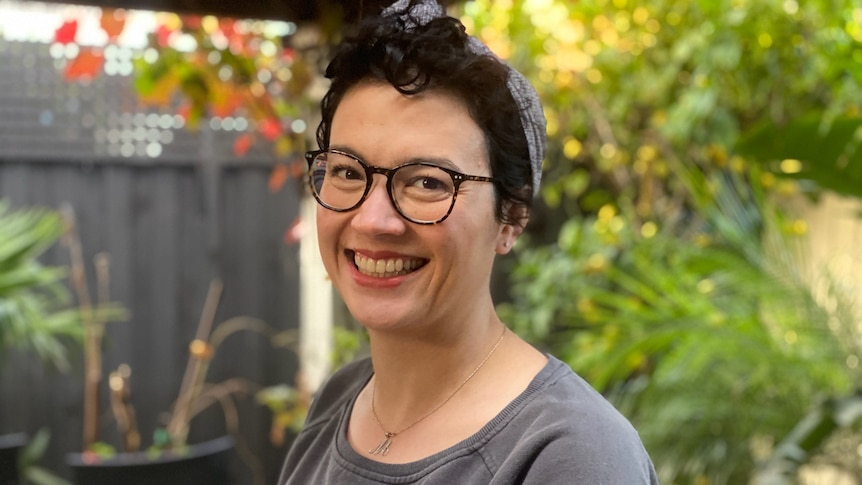 Marianne is smiling. She has short, dark hair and is wearing glasses. She is in a garden setting.