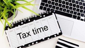 A calendar with tax time written on it beside a computer.