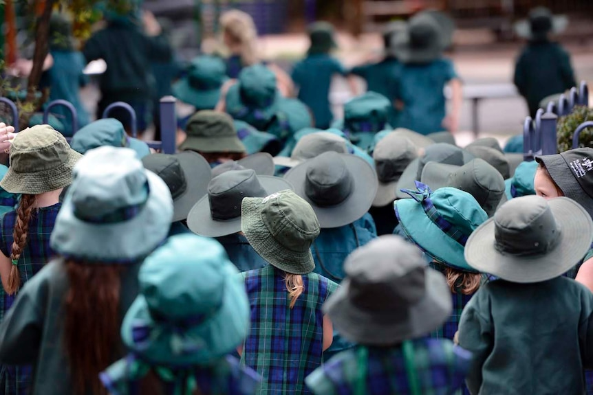 Primary school students wearing green and blue uniforms