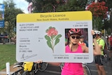 A cyclist holding up a mock bicycle licence at a protest against proposed New South Wales traffic laws.