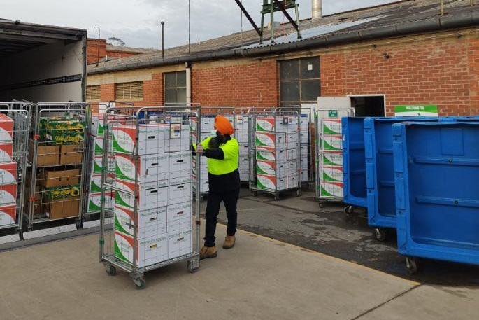 A man wheels a trolley full of boxes to a truck