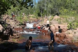 At a small waterfall, some people swim in the water while other sit on the rocks.