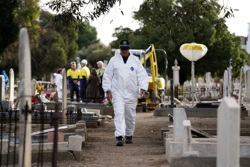 A man in white overalls walks past gravestones as excavation crews work in the background