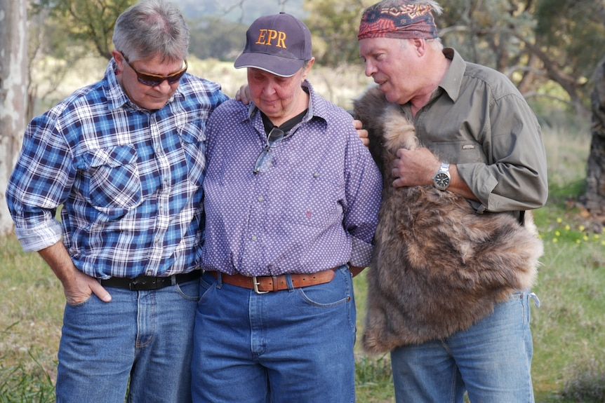 Two indigenous elders embrace a non-indigenous woman, all three are quite emotional