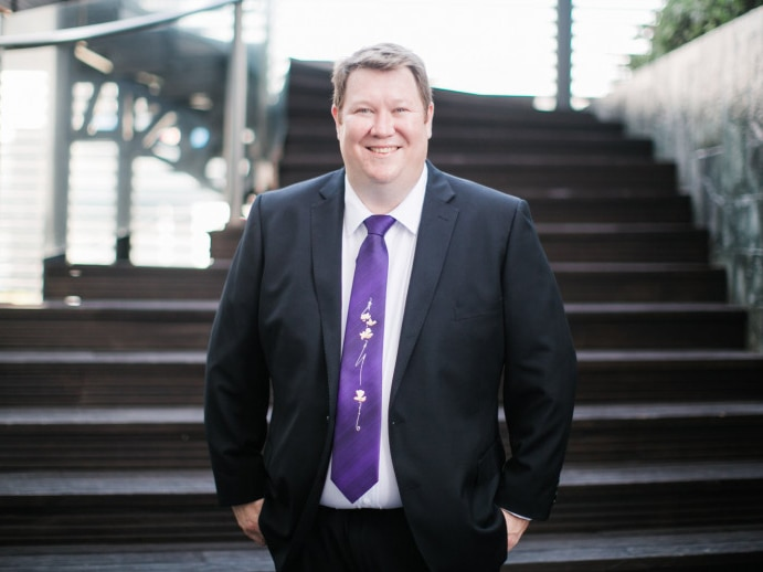 A man wearing a suit and purple tie smiles for the camera at the bottom of a staircase