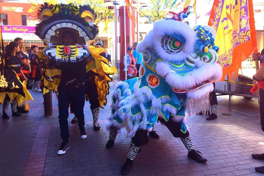 A blue dragon dances in the street.