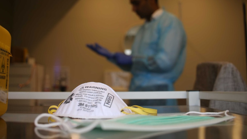 A doctor wears a blue gown and gloves in the background. A P2 mask sits in the foreground.