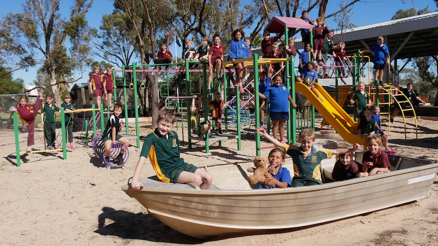 Children in maroon, green, blue and black school shirts play on a playground and old silver boat on a sunny day.
