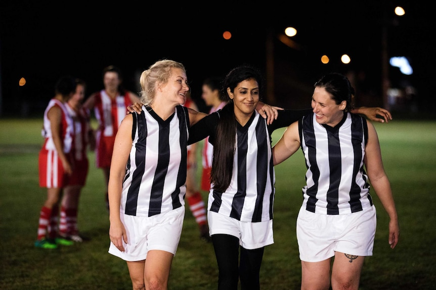 Three women wearing AFL team uniforms are walking on a football oval with their arms around each other and smiling.