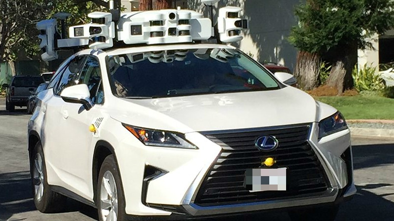 A modern white car has a large contraption, containing what look like multiple cameras and sensors, on its roof
