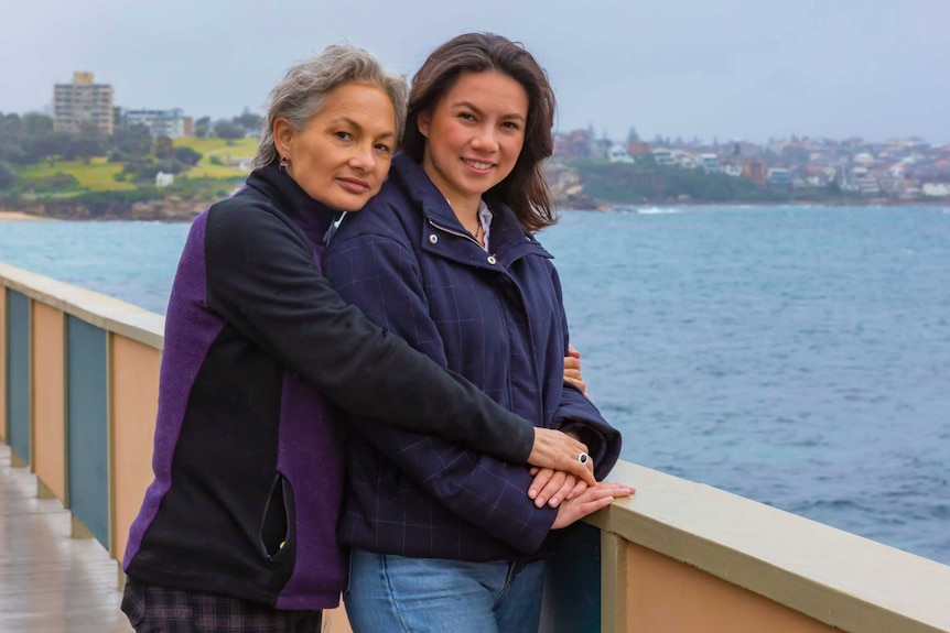 A woman and her adult daughter stand beside the water