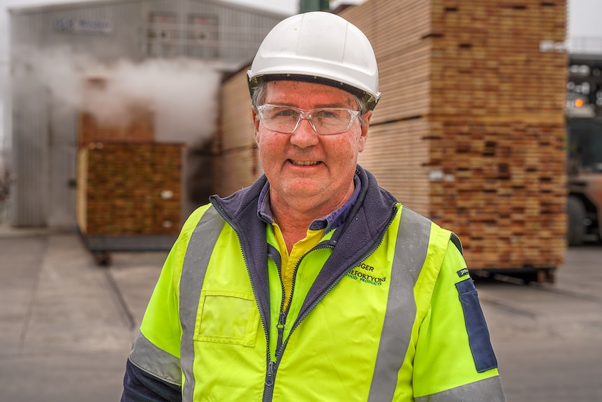 A man in a high vis, hardhat and safety glasses smiles for a photo.