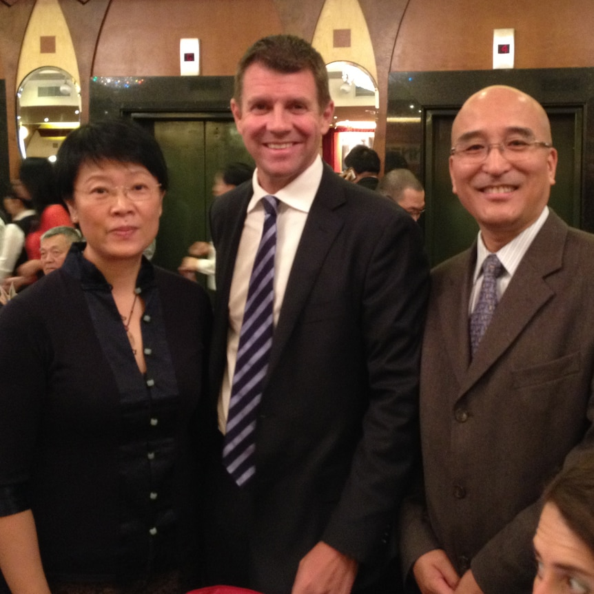 A woman and two men photographed at a restaurant.