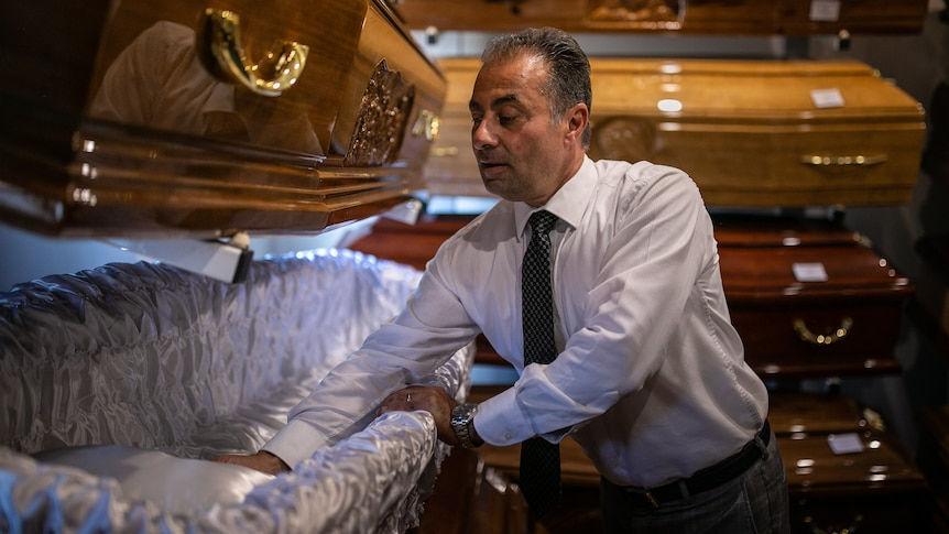 A man wearing a suit examines the satin interior of a coffin on display.