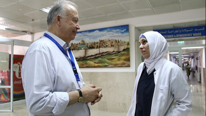Makassad Hospital director Rafik Husseini talks to one of his staff in a hospital corridor.