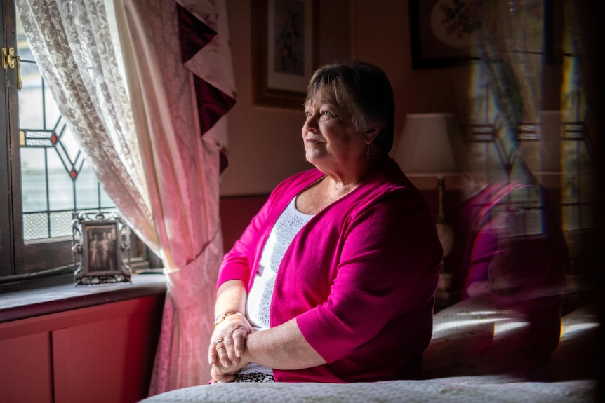 Val Stewart sits, looking out a window, her arms on her lap.