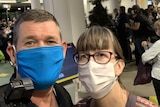 Selfie head shot of a man and a woman wearing face masks at an airport.