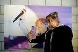 A fan of K-pop boy band BTS, takes a selfie while wearing a face mask at a cafe decorated with their merchandise.