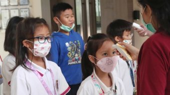 Indonesian school students have their temperature taken