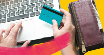 Hands holding a credit card over a laptop