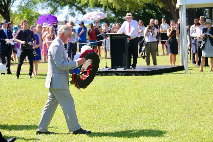 Prince Charles walks across the lawn with a wreath in his hand