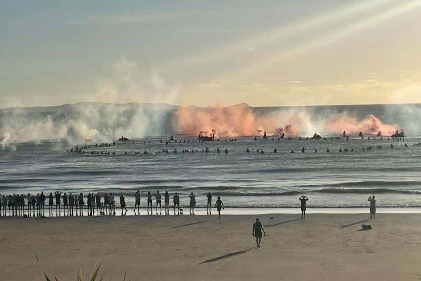 Coloured smoke billows over the water where a group of surfers on boards watch.