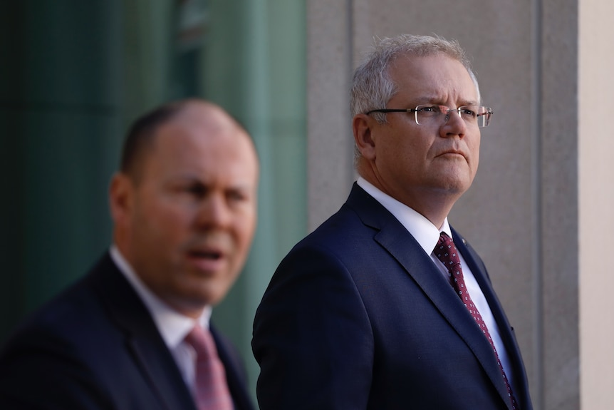 Scott Morrison looks into the distance while listening to Josh Frydenberg at a joint press conference