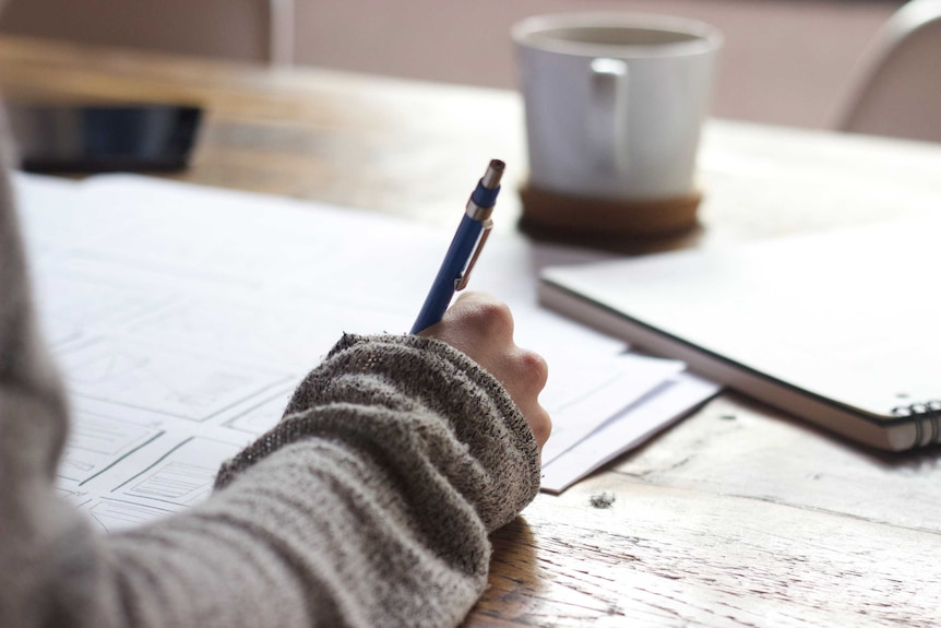 Close up of hand writing on paper with a coffee cup behind