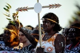 An Aboriginal woman holds a cross prior to a mass at Barangaroo in Sydney.
